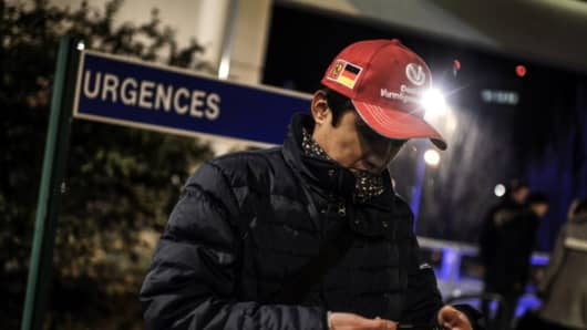 A Scuderia Ferrari and Michael Schumacher fan waits, on December 29, 2013 in Grenoble, in front of the emergency department of the Centre Hospitalier Universitaire hospital.
